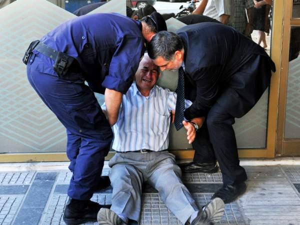Aposentado grego chora na fila em agência bancária em Atenas nesta sexta-feira (3) (Foto: Sakis Mitrolidis/AFP)